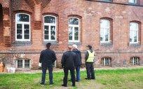 5 osób przed budynkiem szkoły, które sprawdzają wykonane prace związane z wymianą okien