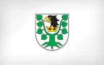 Herb Powiatu Oleckiego. Na jednopolowej hiszpańskiej tarczy herbowej w polu srebrnym głowa orła czarnego z dziobem złotym i takąż koroną na szyi, pomiędzy dwoma konarami lipy zielonej, z których każdy ma cztery liście.
