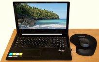 Widok na biuro z uruchomionym laptopem. Na ekranie widok na skaliste wybrzeże.